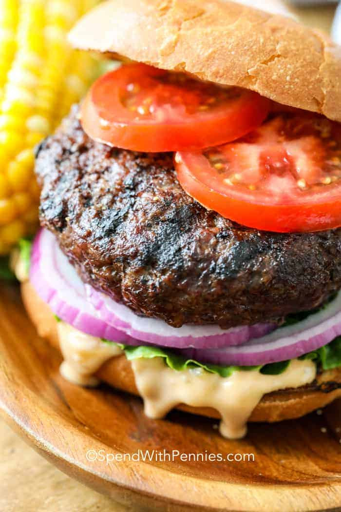 Close up of a juicy hamburger assembled with tomatoes, red onions, lettuce and sauce.