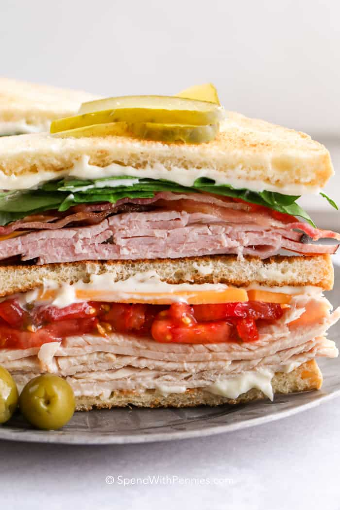 A club sandwich cut in half and served with pickles and olives