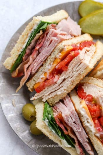 Pieces of club sandwich on a plate with olives and pickles