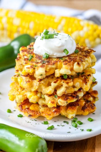 Corn Fritters stacked on a plate with sour cream
