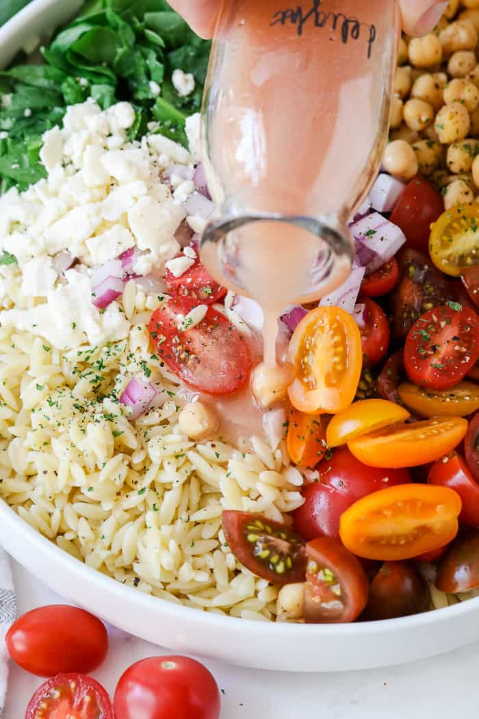 Close up of orzo pasta salad ingredients in a bowl with dressing being poured over top.