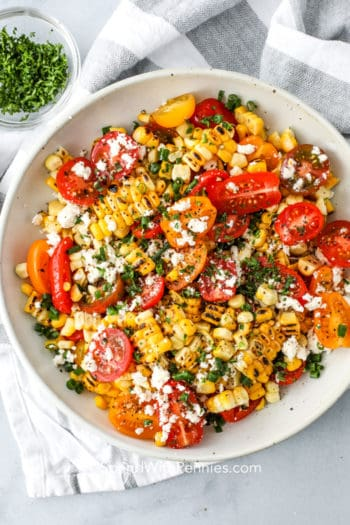 Grilled corn salad in a white bowl with parsley and feta on top