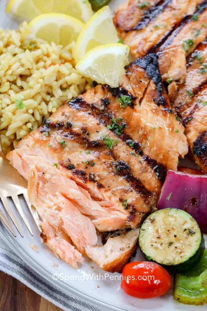 Close up of a grilled salmon fillet plated with roasted veggies, rice and lemon slices. A piece has been pulled off revealing how flakey and tender it is.