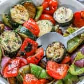 White bowl filled with grilled veggies with a spoon