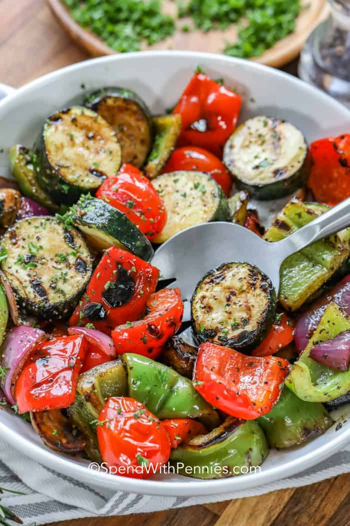 Grilled vegetables in a bowl with a scoop being served.
