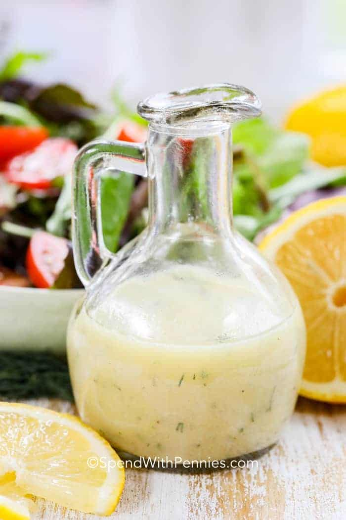 Lemon vinaigrette dressing in a glass bottle with a fresh tossed salad