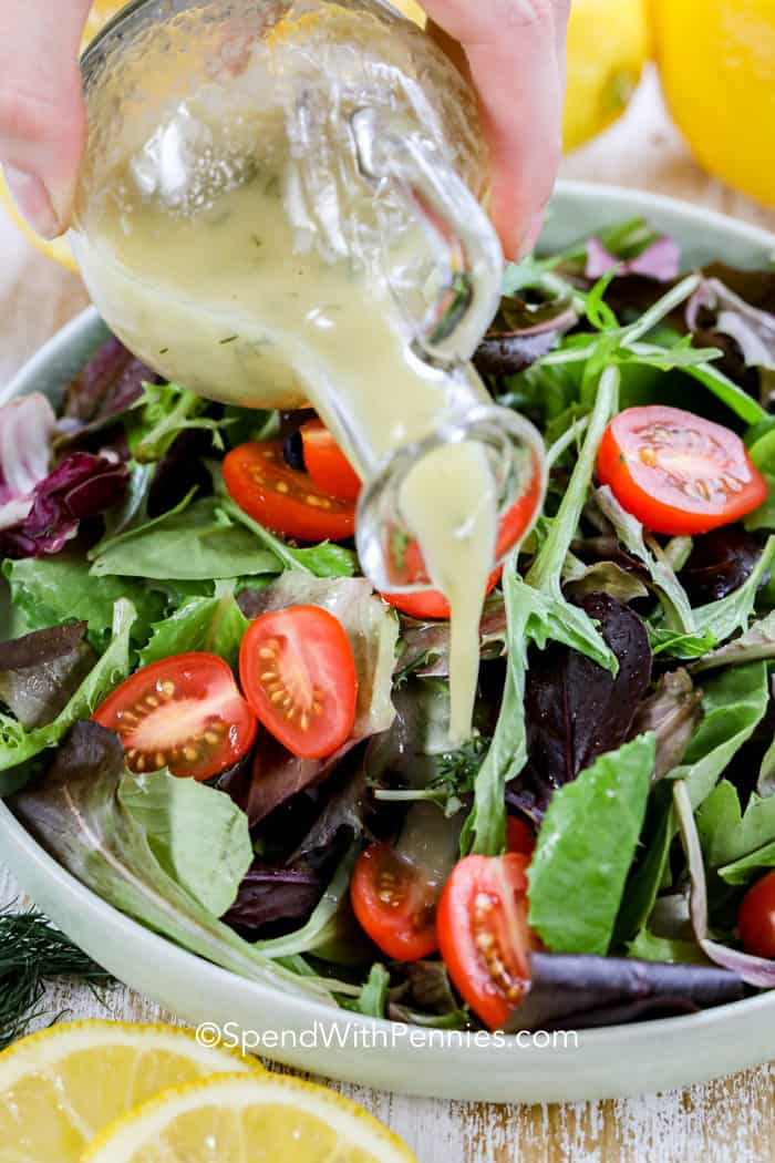 Pouring homemade lemon vinaigrette over a fresh tossed salad in a bowl.