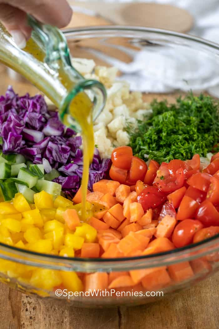 Bowl of chopped salad ingredients with dressing being poured on top.