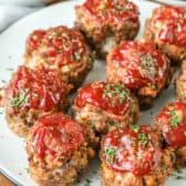 Meatloaf Muffins on a plate with vegetables in the background
