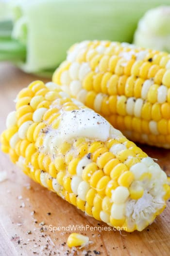 Corn on the cob on a wooden board with butter and pepper