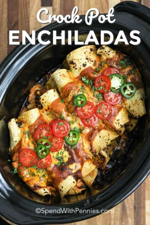 Enchiladas piled in a slow cooker and garnished with tomatoes and jalapenos