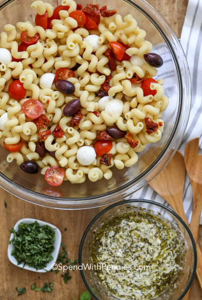 Pesto pasta salad prepared in a glass bowl with the basil and dressing on the side.