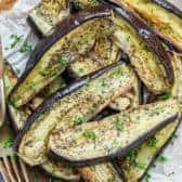 Roasted eggplant on parchment paper with a fork