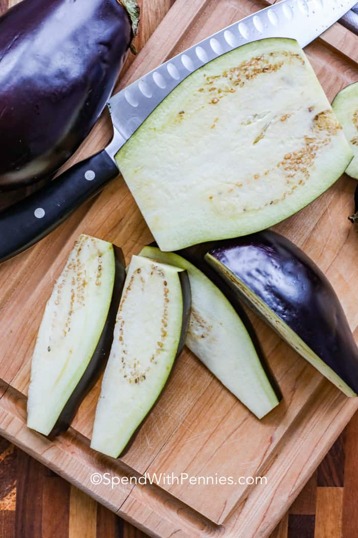 Eggplant being cut into pieces on a wooden board