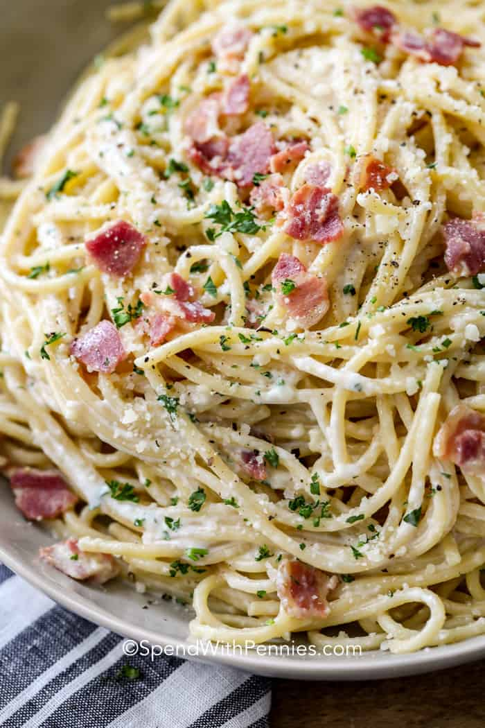 A close up shot of spaghetti carbonara with pancetta and green parsley.