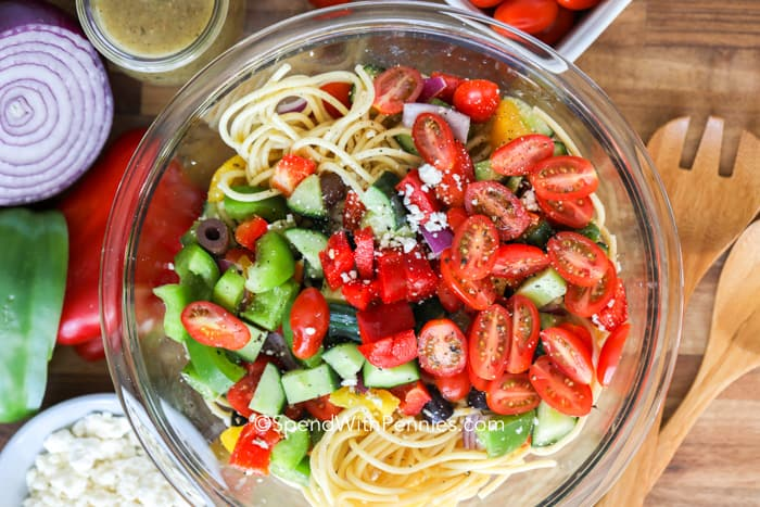 Spaghetti salad ingredients in a clear Bowl before being mixed