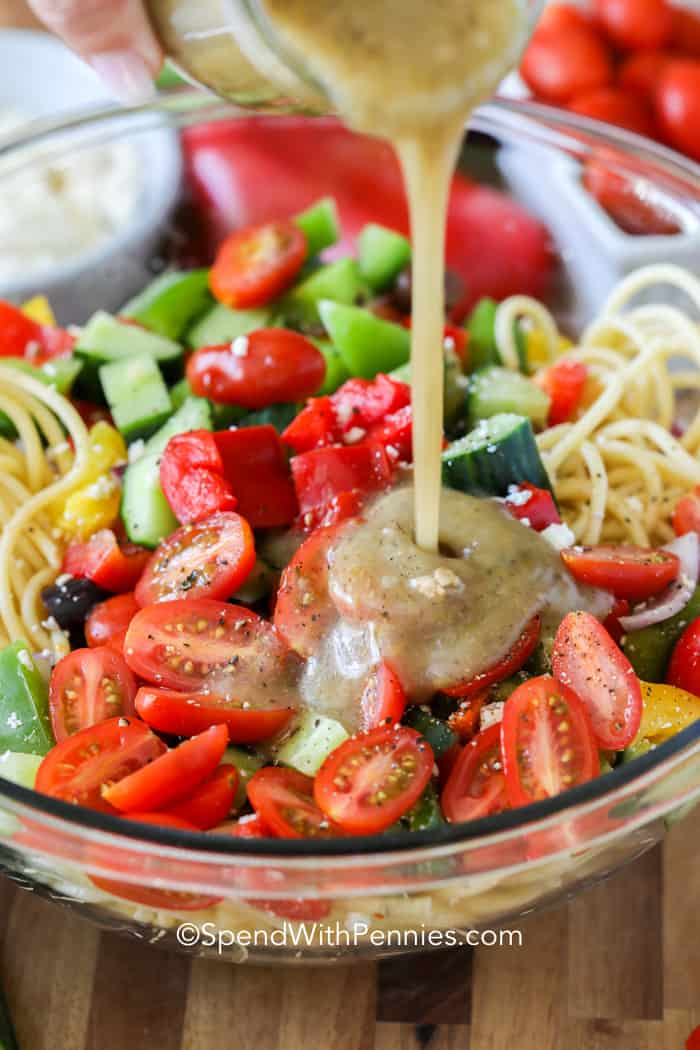 Spaghetti salad in a clear bowl with dressing being poured on