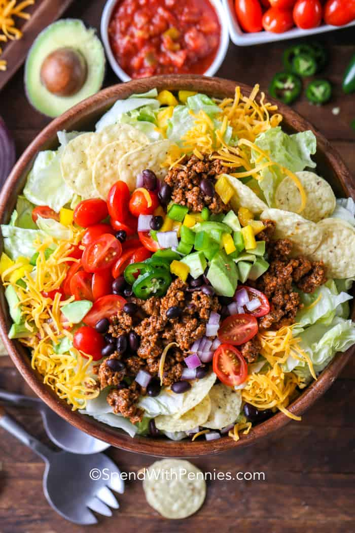 Taco salad in a wooden Bowl with serving spoons on the side
