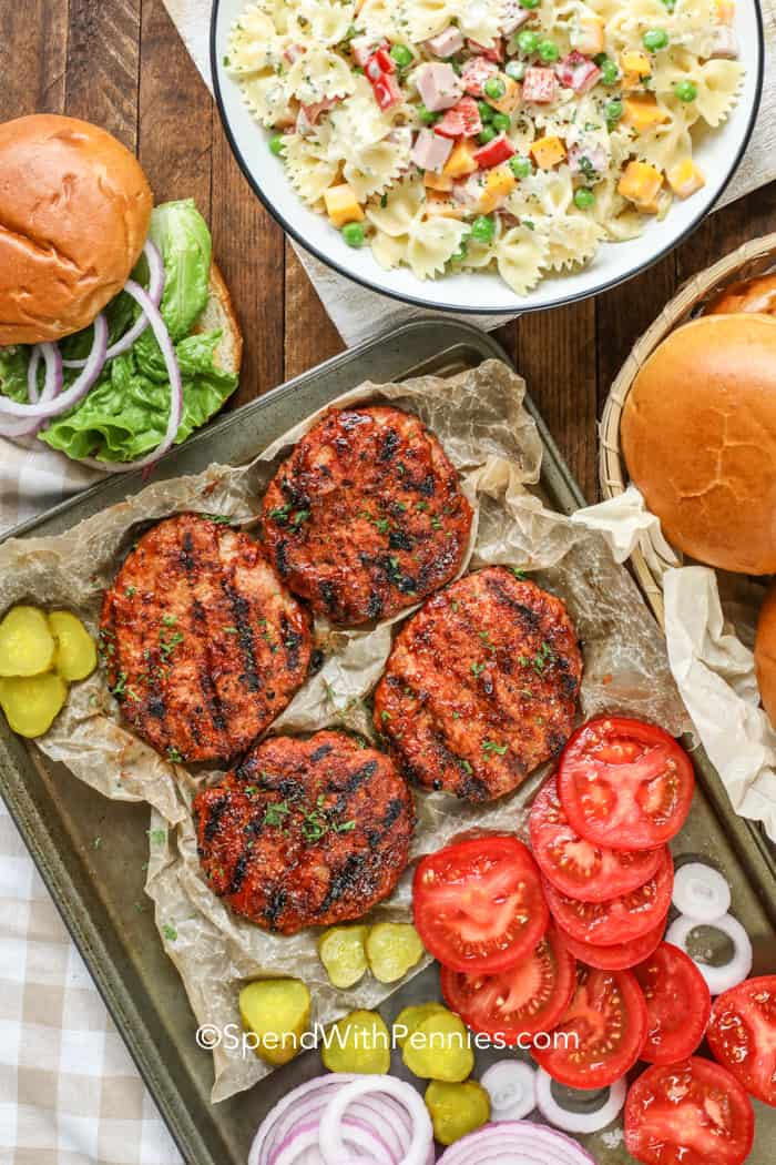 Turkey burgers on a baking pan with slices pickles, tomatoes, and onions.