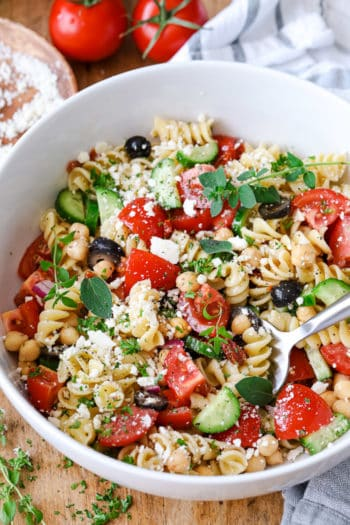 Mediterranean Pasta Salad topped with fresh herbs