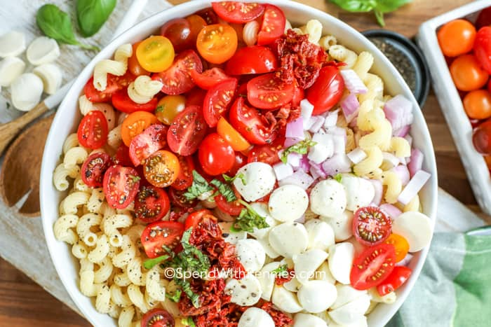Caprese pasta salad ingredients in a bowl.