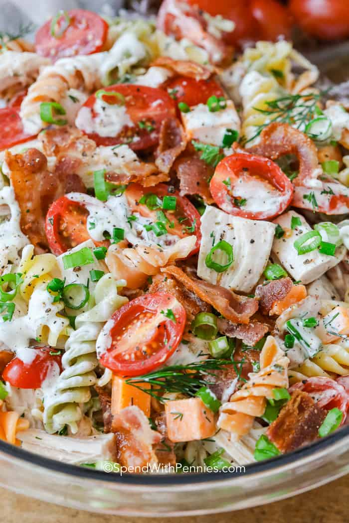 Ranch Chicken Pasta Salad ingredients mixed topped with herbs and onions
