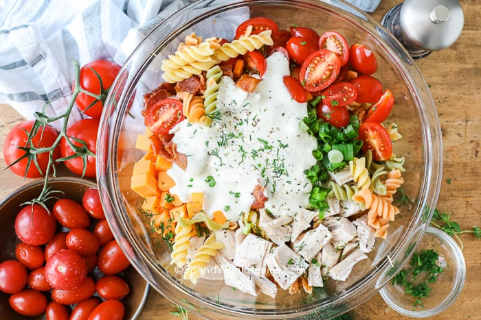 Overview of chicken pasta salad ingredients and dressing on top, in a glass bowl before being mixed.