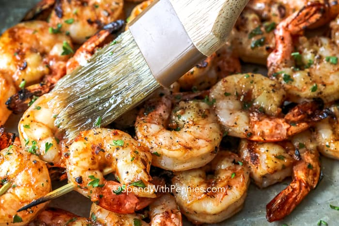 Shrimp skewers being brushed with a tangy marinade.