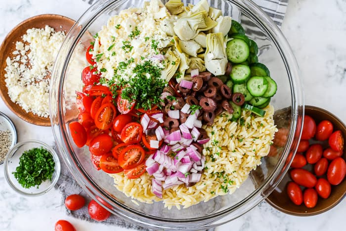 A bowl of orzo salad ingredients including tomatoes, cucumbers, olives, onions and cheese