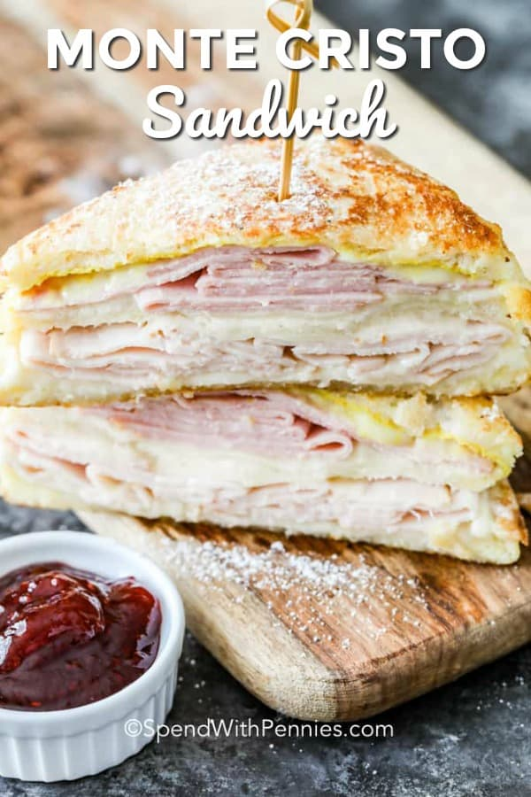 Monte Cristo sandwich on a wooden board with sauce on the side with writing