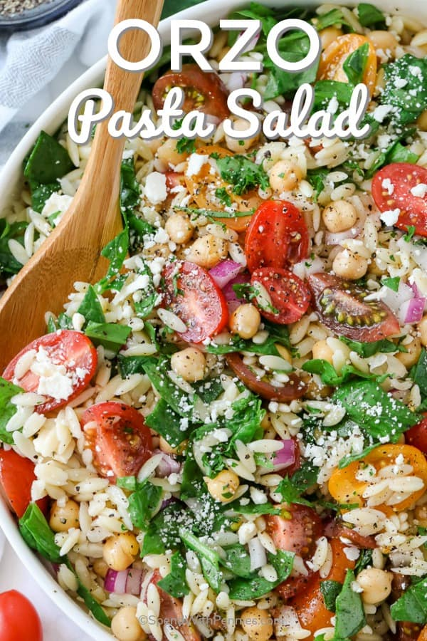 This simple orzo spinach pasta salad is a Mediterranean twist on a classic. Made with feta, tomatoes, and garbanzo beans, tossed in a lemony dressing, it is an easy and healthy summer salad. Serve cold at your next barbecue! #spendwithpennies #orzopastasalad #pastasalad #sidedish #Mediterranean #summerrecipes