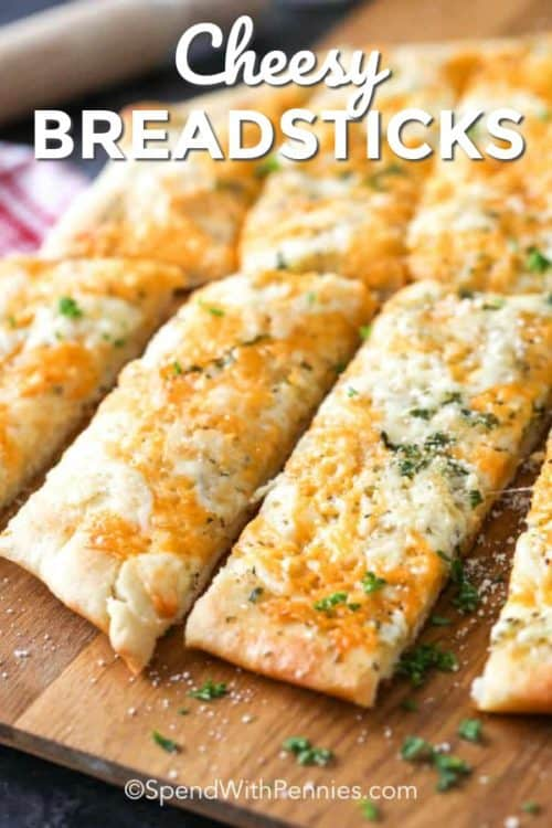 Breadsticks served on a wooden board and garnished with parsley