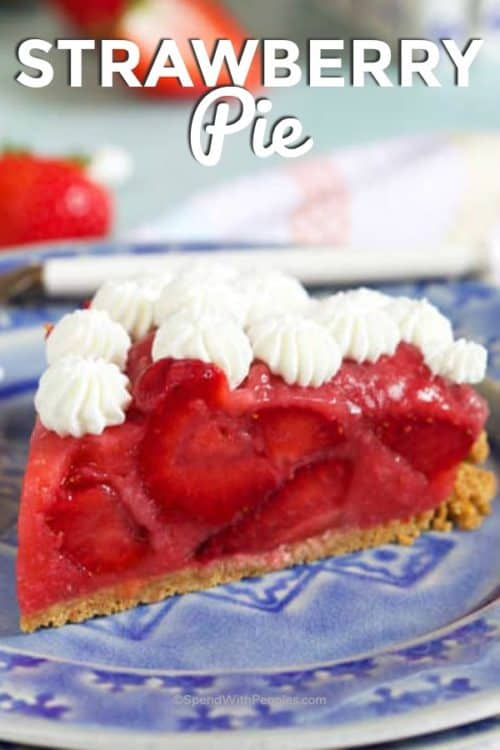 A slice of strawberry pie garnished with whipped cream buds and served on a blue plate