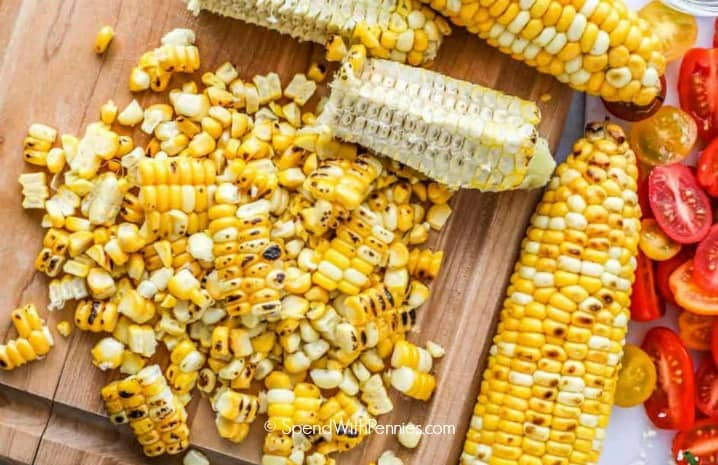 Grilled corn cut off of the cob on a cutting board to make corn salad