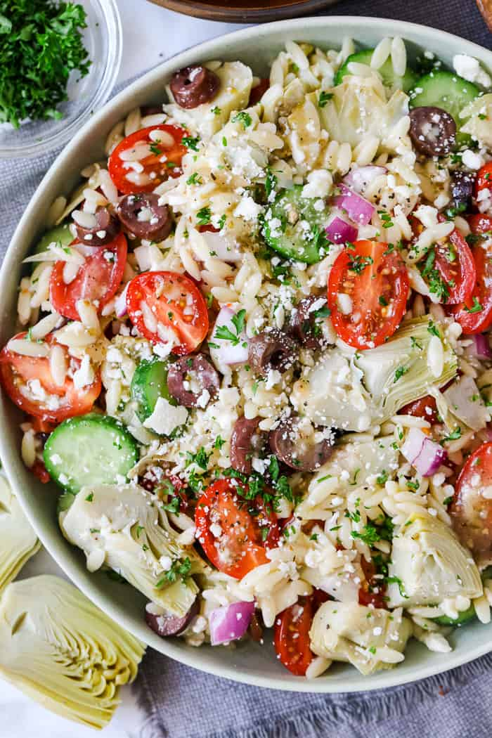 Orzo Salad in a bowl topped with feta cheese and parsley