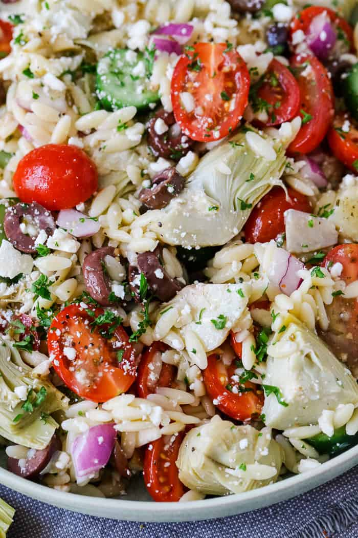 A photo of a tossed orzo salad with tomatoes, artichokes, cucumbers, onions and olives