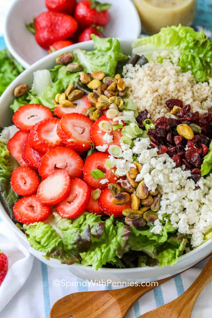 A bowl of pistachio strawberry salad filled with fresh ingredients like feta, cranberries, quinoa, and lettuce.