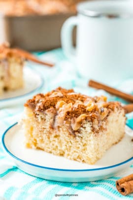 Slice of cinnamon coffee cake on a small dessert plate on a blue and white napkin.