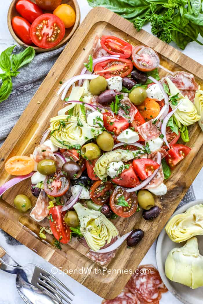 antipasto ingredients mixed together on a board, including cheeses, olives, tomatoes, salami and artichokes
