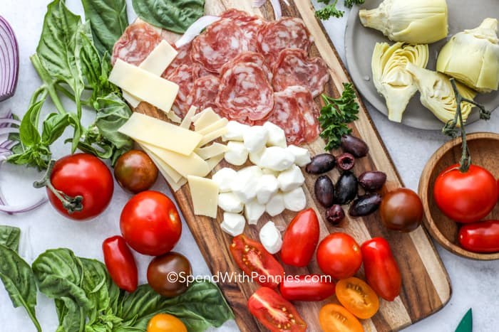 antipasto ingredients laid out on a board, including cheeses, olives, tomatoes, salami and artichokes