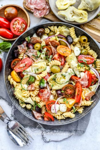 Antipasto Pasta Salad in a bowl with ingredients around it