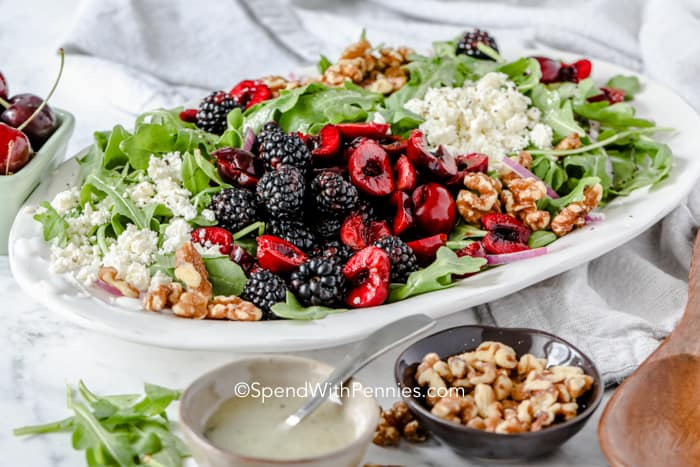 Arugula Salad on a white serving tray with dressing and pecans on the side.