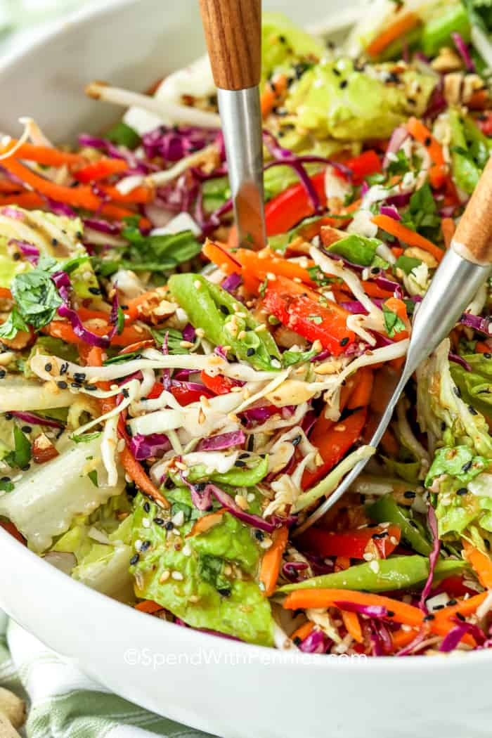 Asian chopped salad ingredients being combined with salad spoons.