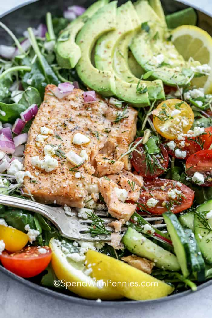 taking a forkful of Avocado Salmon Salad with salmon, tomatoes, cucumbers and cheese