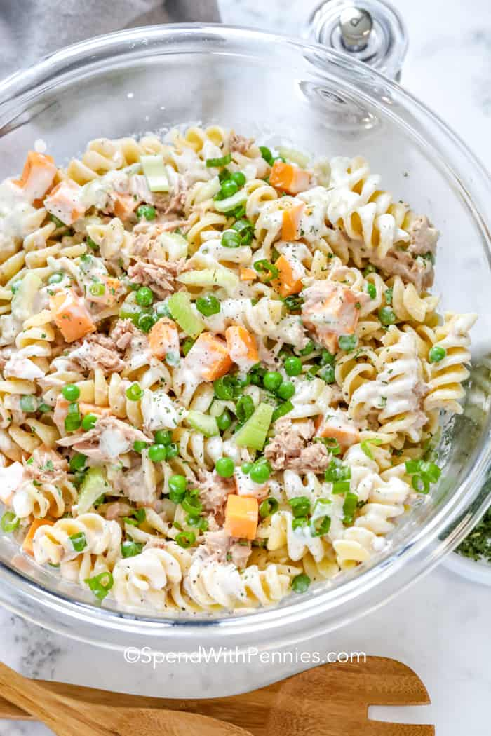 Pasta with tuna, cheese, peas and celery all tossed with a creamy dressing, in a clear bowl