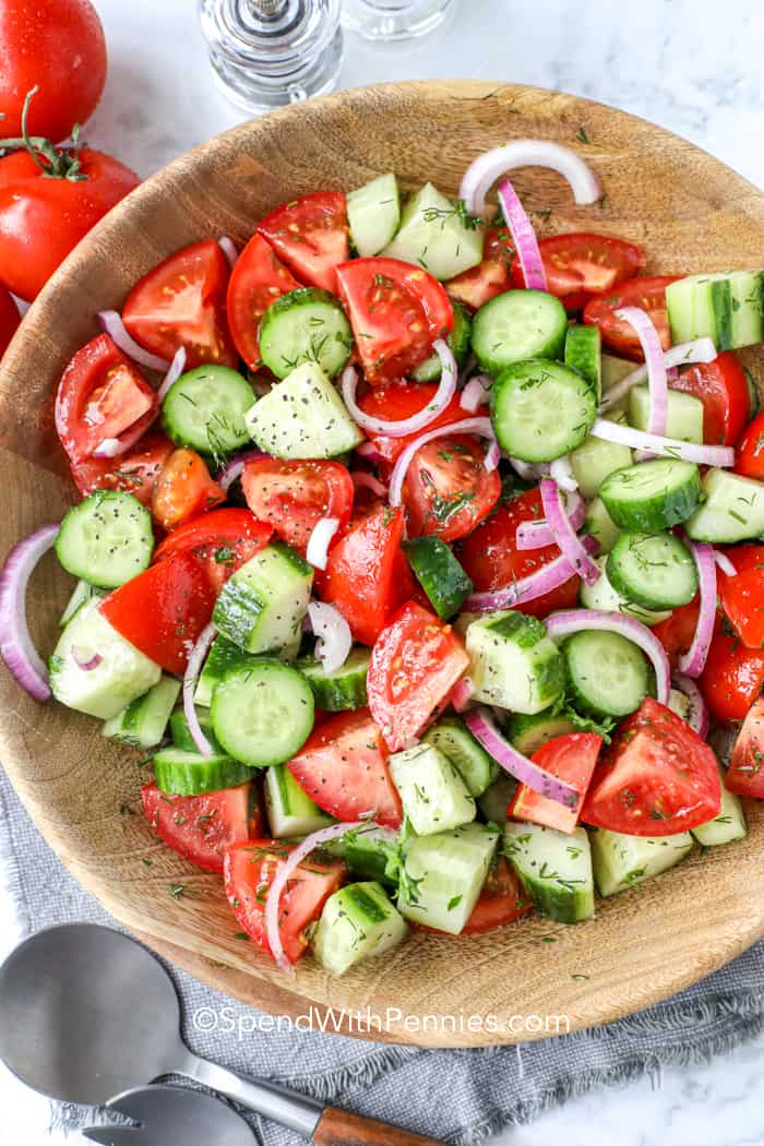 Cucumber tomato salad in a wooden bowl.