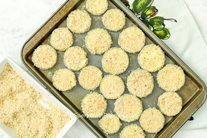 Zucchini slices breaded on a baking sheet.