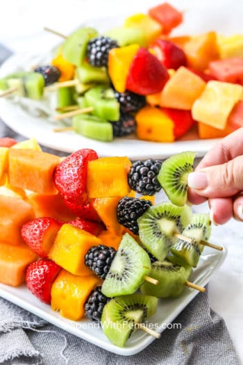 taking a fruit kabob from a plate full of fruit kabobs
