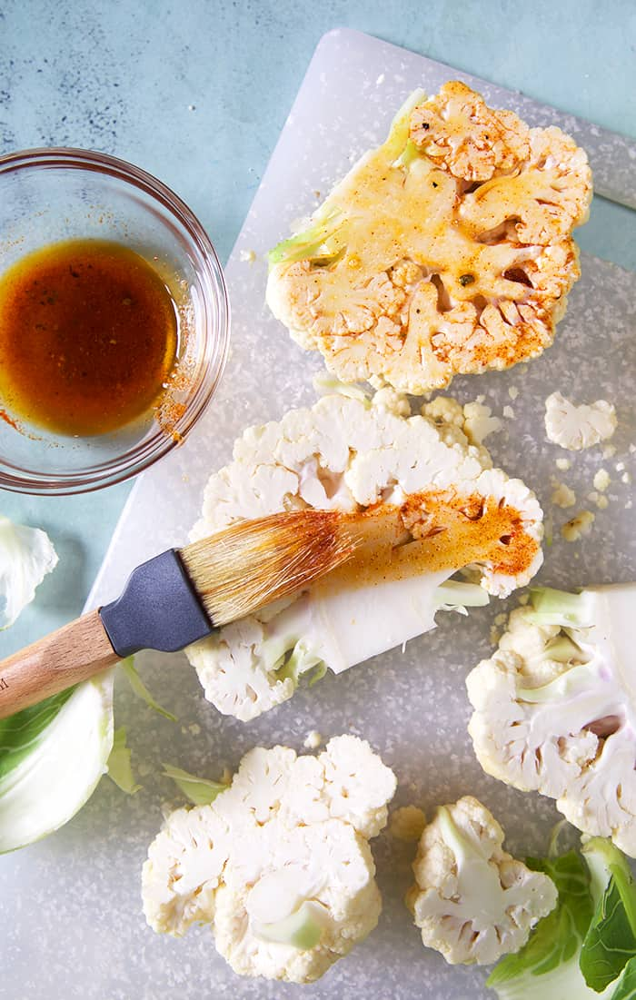 Cauliflower Steaks being brushed with a seasoned oil on a cutting board.