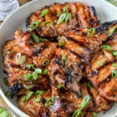 Grilled Chicken Thighs in a bowl with green onions and sesame seeds